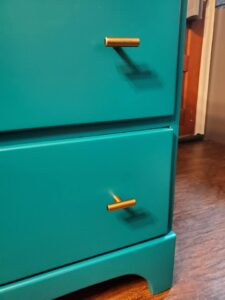 Hint of refinished dresser with bright jade color and contemporary gold bar drawer knobs
